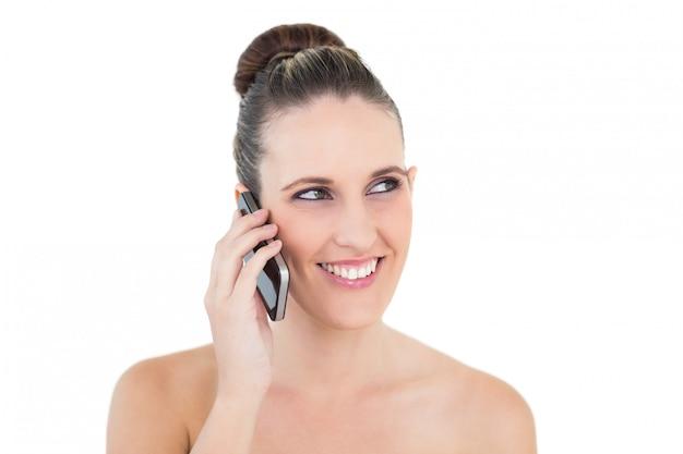 Uśmiechnięta kobieta patrzeje daleko od na telefonie