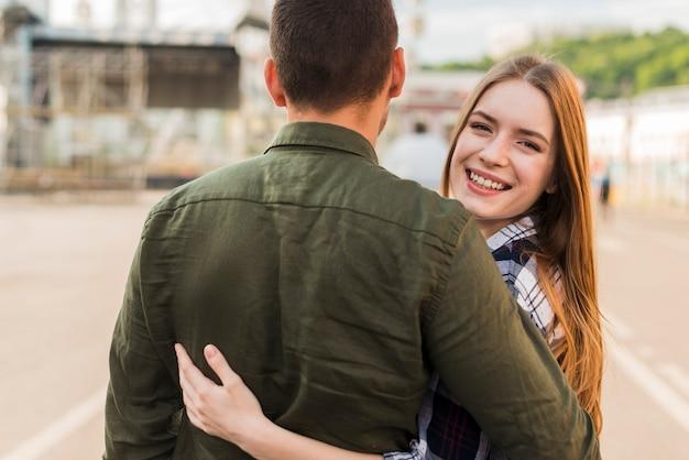 Uśmiechnięta kobieta patrzeje kamerę podczas gdy ściskający jej chłopaka