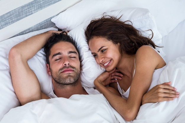 Uśmiechnięta kobieta patrzeje mężczyzna relaksuje na łóżku