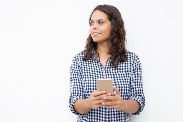 Uśmiechnięta kobieta patrzeje na boku z telefonem komórkowym
