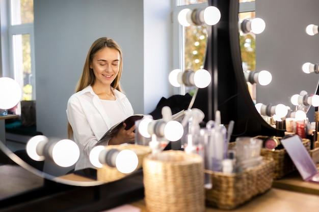 Uśmiechnięta kobieta patrzeje przez magazynu