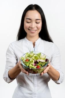 Uśmiechnięta kobieta patrzeje puchar zdrowa sałatka przeciw białemu tłu