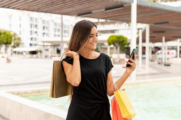 Uśmiechnięta kobieta patrzeje smartphone