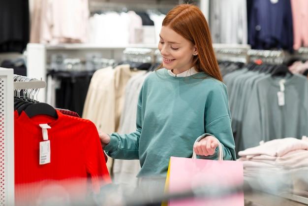 Uśmiechnięta kobieta patrzeje ubrania