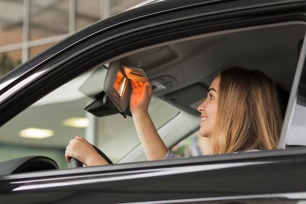 Uśmiechnięta kobieta patrzeje w samochodowym lustrze