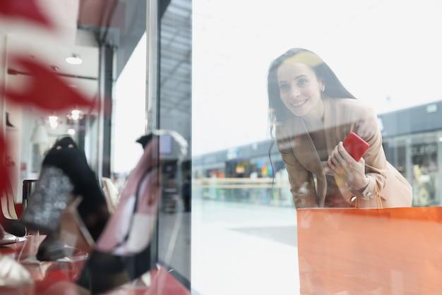 Uśmiechnięta kobieta patrzy na witrynę sklepu z damskimi butami