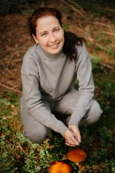 Uśmiechnięta kobieta patrzy w kamerę po znalezieniu jadalnych grzybów w leśnej koncepcji ekoturystyki