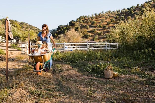 Uśmiechnięta kobieta pcha dwa córki siedzi wśrodku wheelbarrow w polu