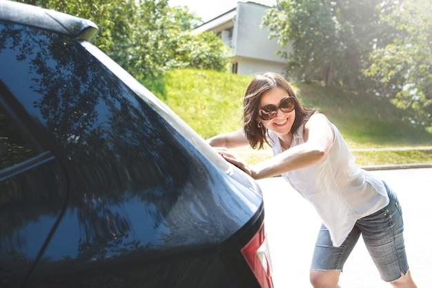 Uśmiechnięta kobieta pcha zepsuty samochód, podczas gdy jej chłopak prowadzi