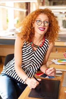 Uśmiechnięta kobieta. piękna rudowłosa kręcona kobieta ubrana w pasiastą bluzkę uśmiechnięta szeroko broad