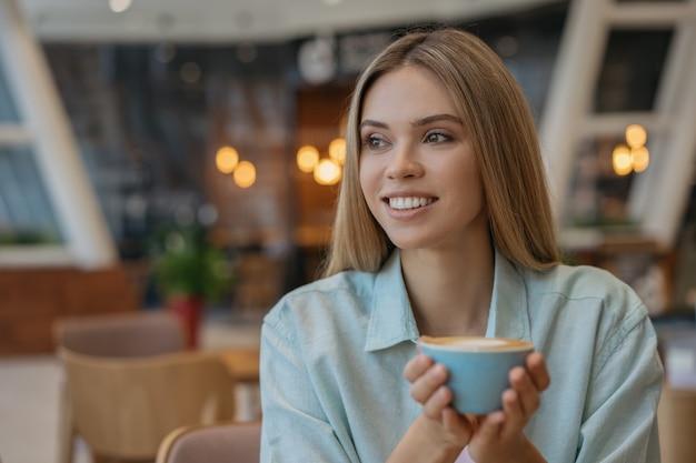 Uśmiechnięta kobieta pije kawę w kawiarni. szczęśliwa kobieta trzyma kubek z gorącym napojem. koncepcja przerwy na kawę