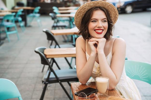 Uśmiechnięta kobieta pije kawę w sukni i słomkowym kapeluszu