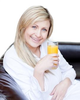 Uśmiechnięta kobieta pije pomarańczowego jus
