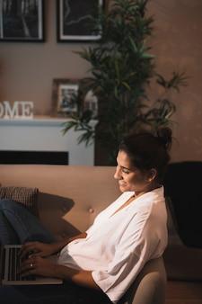 Uśmiechnięta kobieta pisać na maszynie na laptopie