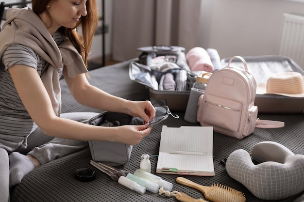 Uśmiechnięta kobieta pisze listę niezbędnych kosmetyków, przygotowując się do organizacji przechowywania wyjazdów wakacyjnych