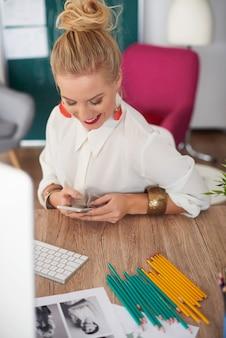 Uśmiechnięta kobieta pisze na swoim telefonie komórkowym
