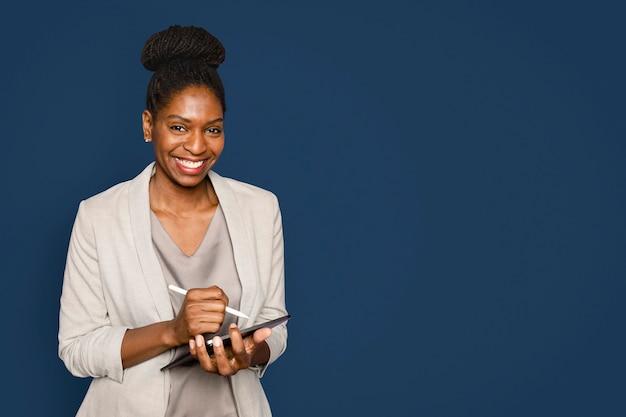 Uśmiechnięta kobieta pisze notatki na urządzeniu cyfrowym typu tablet