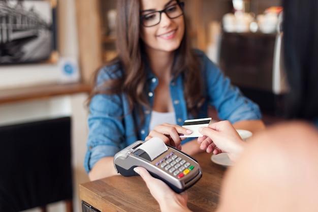 Uśmiechnięta kobieta płaci za kawę kartą kredytową