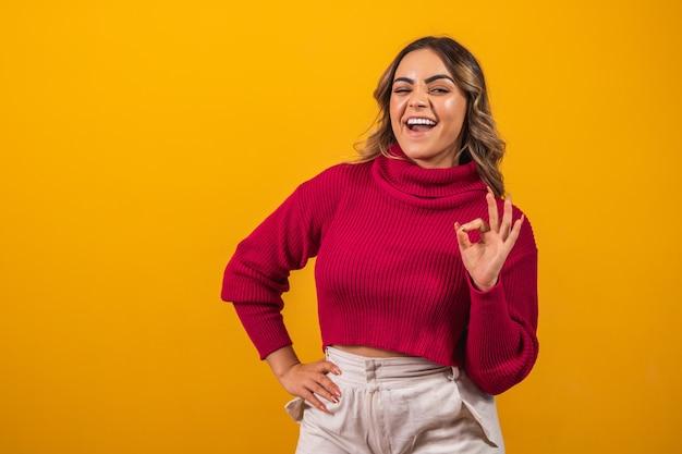 Uśmiechnięta kobieta plus size robi ręką znak ok