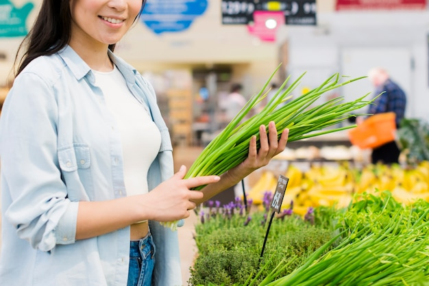 Uśmiechnięta kobieta podnosi zieleni w sklepie spożywczym