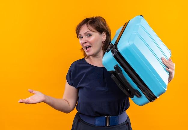 Uśmiechnięta kobieta podróżnik w średnim wieku, trzymając walizkę na punktach ramion, z ręką na bok
