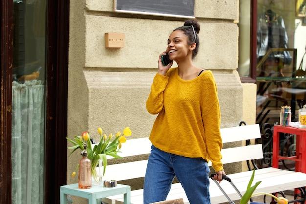 Uśmiechnięta kobieta podróżuje z torbą i telefonem komórkowym