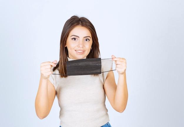 Uśmiechnięta kobieta pokazując czarną medyczną maskę na białym tle.