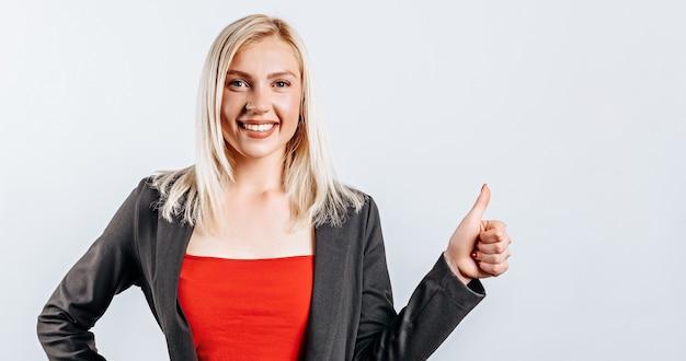 Uśmiechnięta kobieta pokazując kciuki do góry i patrząc w kamerę na białym tle. pozytywna dziewczyna pokazuje jak. dobrze