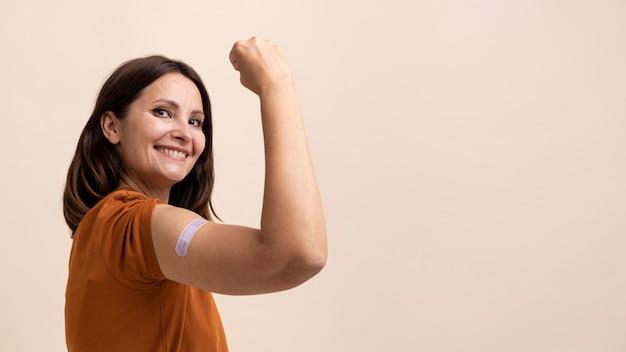 Uśmiechnięta kobieta pokazująca naklejkę na ramieniu po otrzymaniu szczepionki