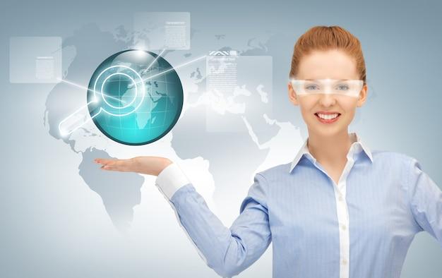 Uśmiechnięta kobieta pokazująca wirtualną kulę ziemską na dłoni