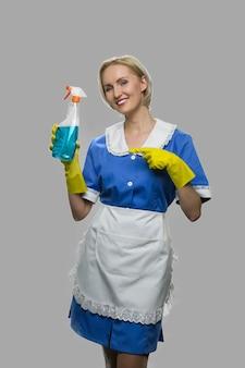 Uśmiechnięta kobieta pokazuje detergent do czyszczenia. śliczna pokojówka oferująca spray do czyszczenia na szarym tle. usługa sprzątania domu.