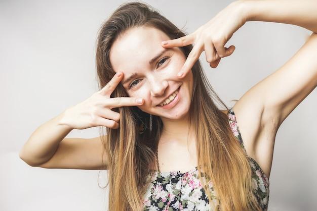 Uśmiechnięta kobieta pokazuje dwa kciuki, spokój, piękny uśmiech, zdrowe zęby