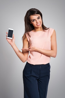 Uśmiechnięta kobieta pokazuje ekran współczesnego telefonu komórkowego