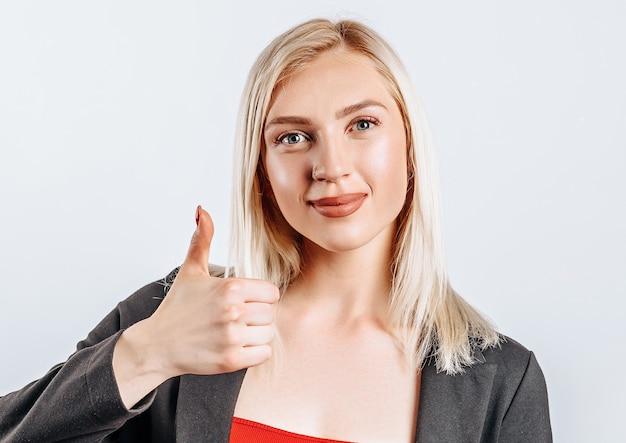 Uśmiechnięta kobieta pokazuje kciuki i uśmiecha się na szarym tle na białym tle