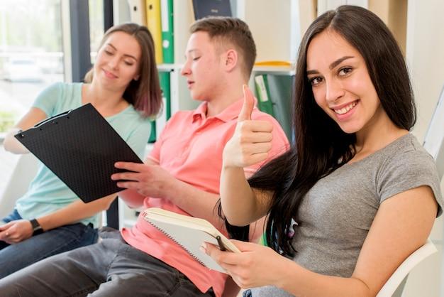 Uśmiechnięta kobieta pokazuje kciukowi up gest siedzi obok jej przyjaciół trzyma schowek