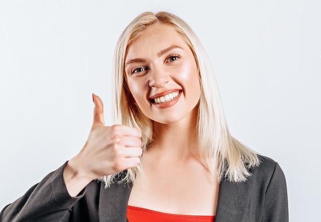 Uśmiechnięta kobieta pokazuje ok kciuki i patrząc w kamerę na na białym tle