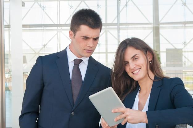Uśmiechnięta kobieta pokazuje skoncentrowanych mężczyzna dane na pastylce