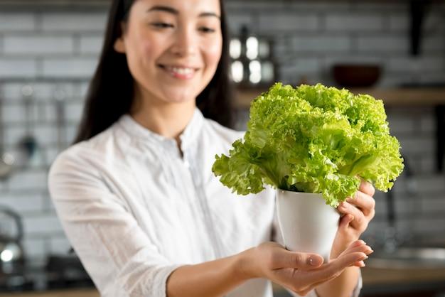 Uśmiechnięta kobieta pokazuje zieloną świeżą sałatę w garnku
