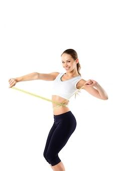 Uśmiechnięta kobieta pomiaru jej talii taśmy środka w sportowej