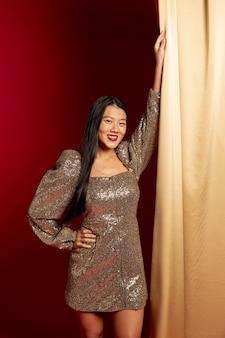 Uśmiechnięta kobieta pozuje w eleganckiej sukni od chińskiego nowego roku
