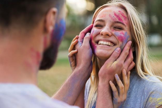 Uśmiechnięta kobieta pozuje z barwioną twarzą