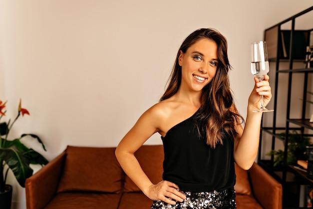 Uśmiechnięta kobieta pozuje z jasnym makijażem i falującymi włosami trzyma kieliszek wina