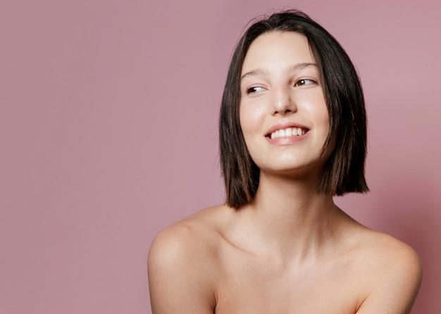 Uśmiechnięta kobieta pozuje z kopii przestrzenią