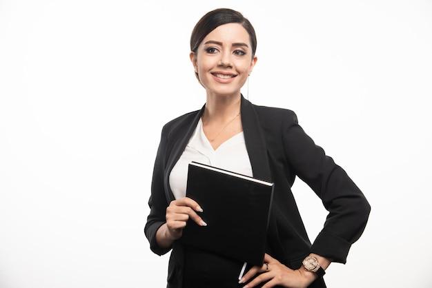 Uśmiechnięta kobieta pozuje z notatnikiem na białym tle. zdjęcie wysokiej jakości
