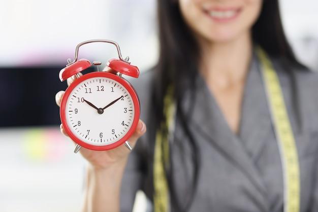 Uśmiechnięta kobieta projektant stylista trzyma czerwony budzik. terminowa realizacja zamówień