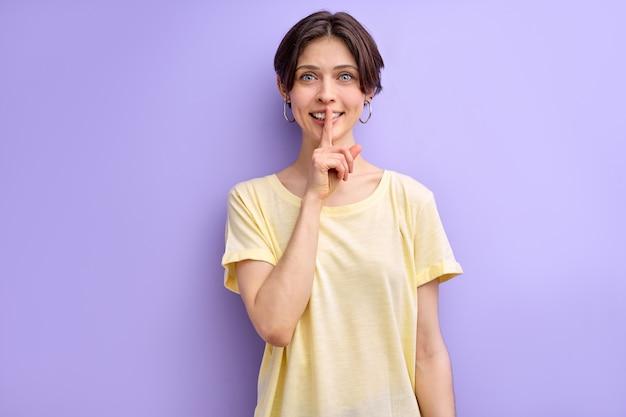 """Uśmiechnięta kobieta prosząca o ciszę i cicho gestykulująca palcem przed ustami, mówiąca """"cii"""" lub dochować tajemnicy przed fioletową ścianą w studio"""