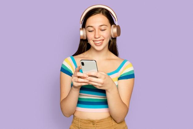 Uśmiechnięta kobieta przesyła strumieniowo muzykę z urządzenia cyfrowego smartfona