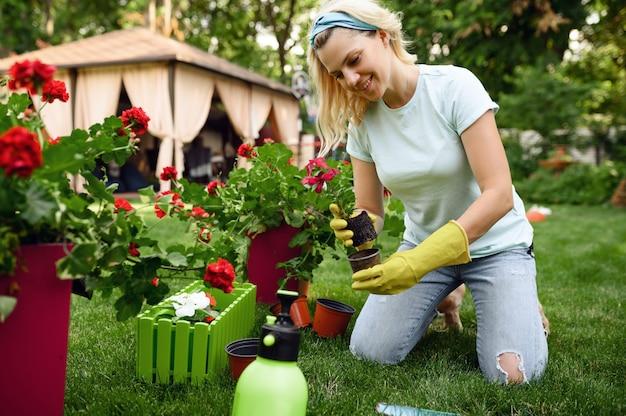 Uśmiechnięta kobieta przeszczepia kwiaty w ogrodzie. kobieta ogrodniczka zajmuje się roślinami outdoorowymi, ogrodnictwem hobbystycznym, florystycznym stylem życia i wypoczynkiem
