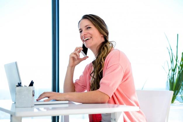 Uśmiechnięta kobieta przy biurku, na swoim laptopie i smartfonie