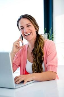 Uśmiechnięta kobieta przy biurku na swoim laptopie i telefonie komórkowym
